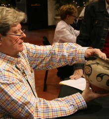 Photograph of appraiser Alston Neal examines a basket at a recent Appraisal Day