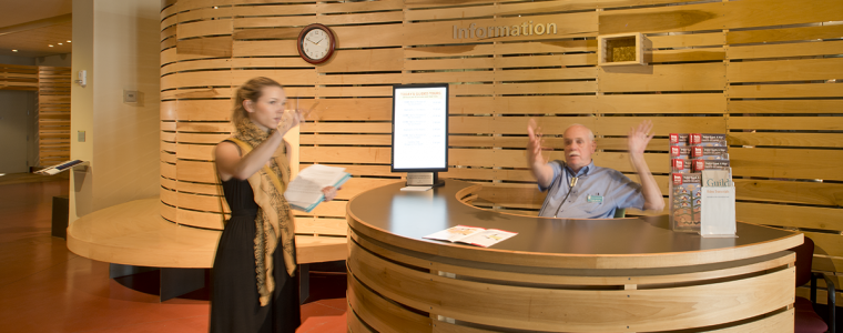 Heard Museum Guild Member giving directions to a visitor at the information desk.