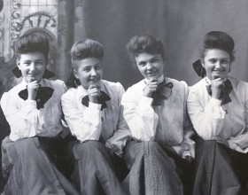 Photograph of five Harvey Girls sitting in a row and smiling at the camera.