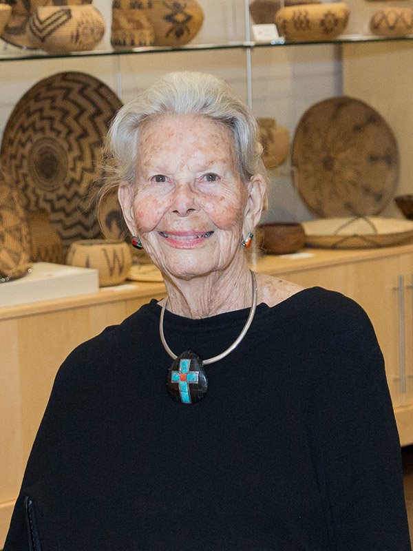 smiling older lady with swept back white hair, black shirt and Native American artwork in background