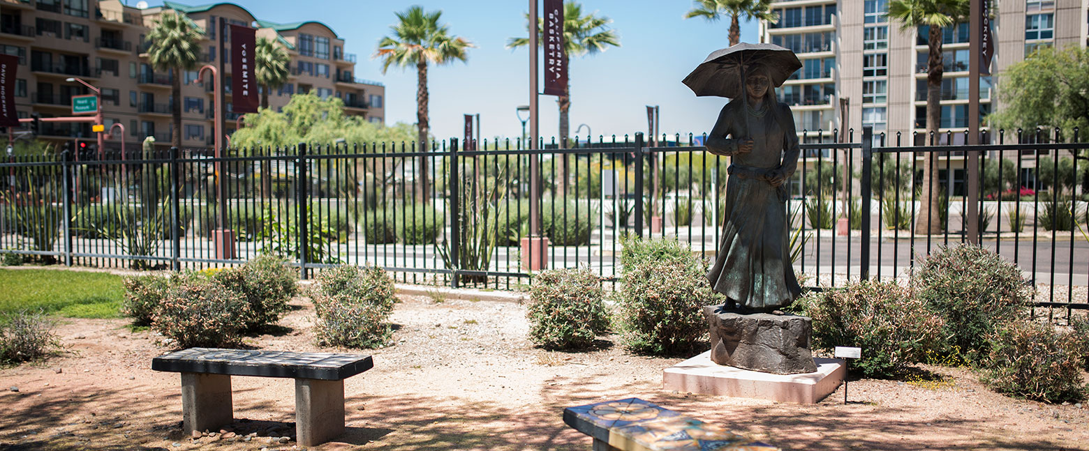 urban desert landscape with wrought iron fence behind bronze sculpture of woman in long dress with umbrella