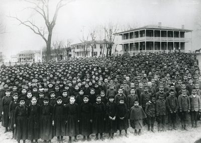 Black and white photo of school children in uniforms, black dresses on the girls and military style jackets and pants on the boys
