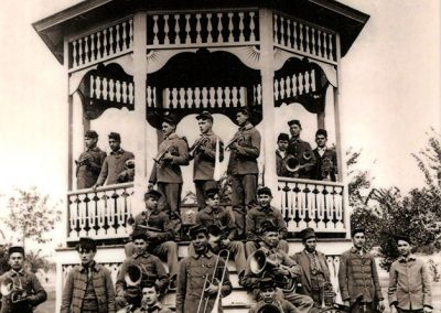 1904 black and white photo of all-male Native band posing with their instruments at a gazebo