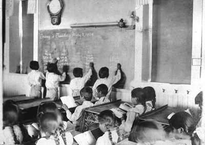 Black and white photo of children in old school room, 3 boys are writing multiplication tables on a chalkboard.