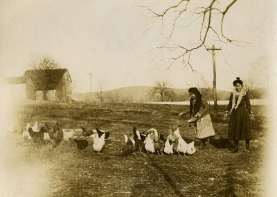 Black and white photo from early 1900s of 2 Native girls feeding chickens. One girl is recognized as Annie Coodlalook.