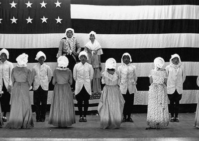 Black and white photo of Native children in colonial costumes on a stage in front of a large American flag