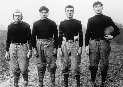 1912 black and white photo of 4 Native youth in early 20th C football uniforms posing for the camera. Jim Thorpe stands at far right holding a football.