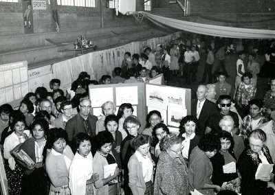 1950 black and white photo of a crowded room with art on panel boards and people looking at it
