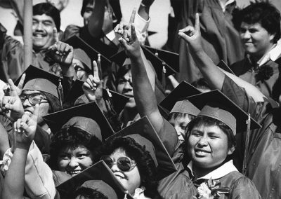 1984 candid black and white photo of Native youth in graduation caps and gowns smiling and holding their right arms in the air with their pointer fingers raised.