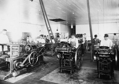 1920 black and white photo of a printing press room with young Native men standing over and working at printing machines.