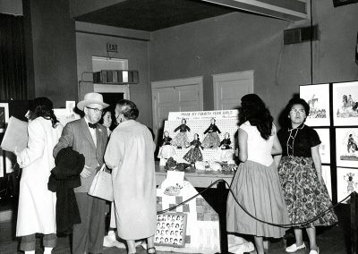 1950 black and white photo of handmade cloth dolls on display at an art event. People mill around looking at the art and talking to each other.