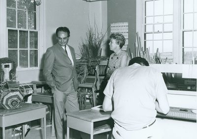 1970 black and white photo of Lloyd Kiva New in a suit standing in weaving classroom with a woman with short blond hair. A young man is hunched over a loom with his back to the camera in the foreground.