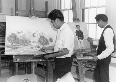 1970 black and white photo of 2 young Native men standing and painting at easels. One paints a landscape and the other paints a portrait of a young boy in traditional Navajo dress.
