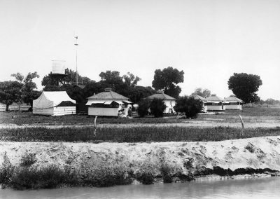 Black and white photograph of land across a body of water with square wooden structures and sparse trees.