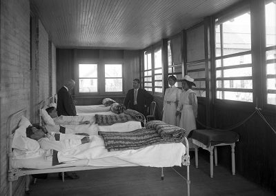 Black and white photo of a turn of the century infirmary. Two doctors and 2 nurses stand by beds with young men.