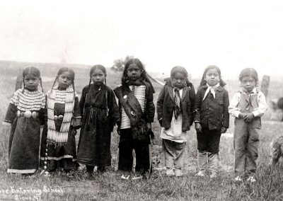 Black and white photo of American Indian children lined up in front of the camera in native dress. Late 19th C.