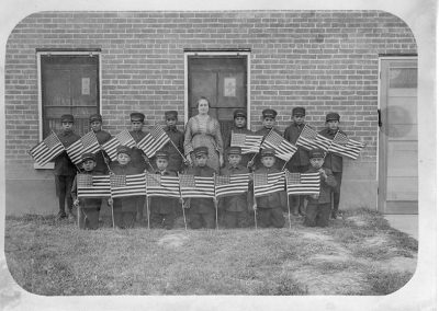 1900 black and white photo of young boys in military style uniforms and caps posing with an older woman in front of a brick building. All the boys hold American flags.