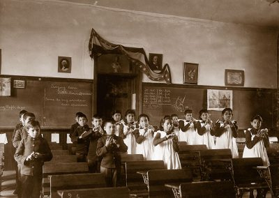 Black and white late 19th C. photo of Native children in uniform standing by their desks making gestures with their hands.