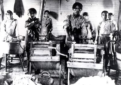 1901 black and white photo of young Native boys in a laundry room in front of wringing machines and wash tubs