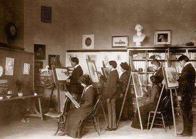 1900 black and white photo of young Native men and women at easels in a drawing still life objects
