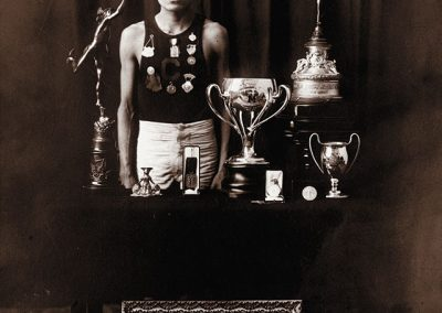 1908 black and white photo of young Native male in track and field shorts and sleeveless top posing with trophies and medals and framed awards including 2 1908 Olympics certificates.