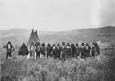 Black and white photo of American Indians in traditional and western dress on the plain in front of a teepee, no date.