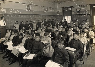 1911 black and white photo of Native children in uniforms seated in classroom with open books