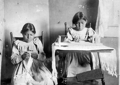 1905 black and white photo of 2 young Native girls working on beading. One girl sits at a desk with a traditional bead loom and the other sits beside with indistinct fabric in her hand.