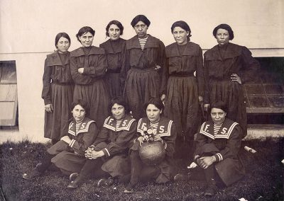 1904 black and white team photo of young Native women basketball players in black sailor style pinafores