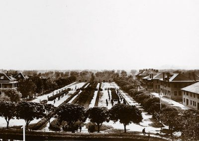 1900 black and white photo aerial view of a center parade grounds with figures lined up and large brick buildings on either side of the grounds.