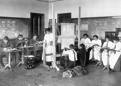 Early 1900s black and white photo of Native youth in an art class weaving and working with fibers