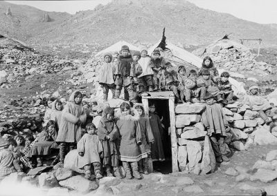 Black and white photo of Alaksan Natives gathered around and on top of a dwelling dug into the ground in a barren rock strewn landscape.