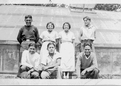 1930 black and white photo of Native youth in western period dress posing for the camera. One of the 2 young women in the photo is Pablita Velarde.
