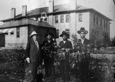 1904 black and white photo of 3 Native youth holding armfuls of turnips next to an older white man in front of a large 2-story brick building