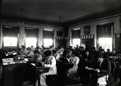 1913 black and white photo of older Native students in a classroom reading at their school desks.