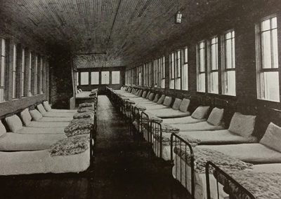 1918 black and white photo of a long narrow wood floor and ceilng room with many windows and single beds lined along the walls.