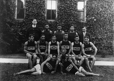 1913 black and white photo of team of young Native men in track and field style shorts and sleeveless shirts posing on lawn in front of an ivy covered building with adult males on either side in the back row.
