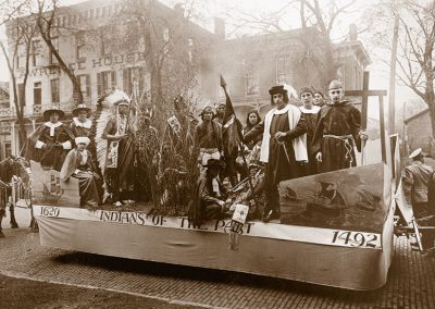 "1920 black and white photo of parade float titled ""Indians of the Past"" showing Native youth in traditional dress, Puritan costumes and Columbus with a priest"