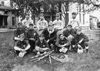 1913 black and white photo of Native youth baseball team with adult male in center. They stand on a grassy lawn with several buildings behind them.