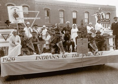 "1920 black and white photo of a parade float titled ""Indians of the Present"" with Native youth posing as nurses, soldiers, cowboars, voting and other modern activities and careers"
