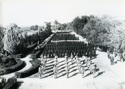 1900 black and white aerial photo of uniformed men and women in formation. A marching band stands in the foreground and the rest of the individuals are in dark uniforms in formation behind them.