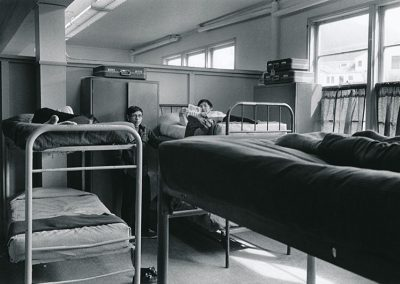 1970 black and white photo of large dorm hall with multiple metal framed bunk beds with 2 young men. One is lounging on an upper bunk reading and the other stands next to the bed.