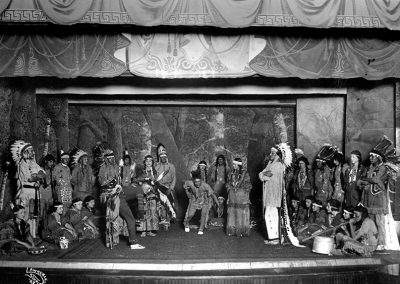 "1922 black and white stage scene of Native students rehearsing in Native dress for the play ""Hiawatha."""