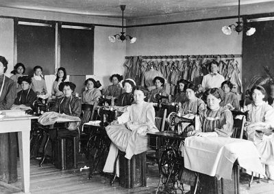 1900 black and white photograph of classroom with Native young women at sewing machines