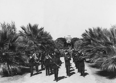 1900 black and white photo of marching band in dark uniforms marching towards the camera on a dirt road between low growing palm trees.