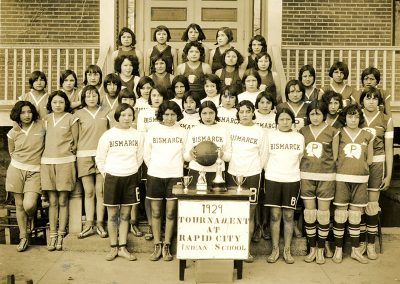 "1929 black and white photo of large group of young Native women from 4 different basketball teams. They pose for the camera in different uniforms with trophies on a table and a banner saying ""1929 Tournament at Rapid City Indian School"" in the foreground."