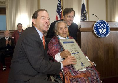 "2006 color photo of an elderly Native woman in a wheelchair posing with 2 Caucasian men. She is holding a plack with her name ""Ester Martinez"" and underneath ""Master Artist."" They are all smiling."