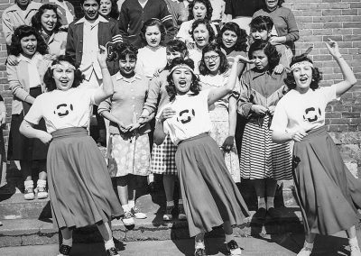 1950 black and white photo fo 3 very animated Native cheerleaders in front of a crowd of students on steps to a building in the background.
