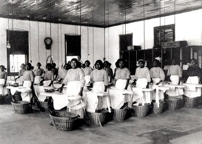 1910 black and white photo of young Native women in a large industrial style laundry room at ironing boards, baskets below.