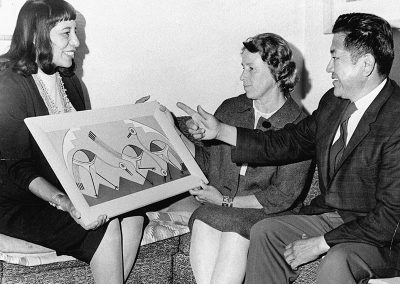 1963 black and white photo of young Native woman happily showing her painting to a Native man and Caucasian woman.